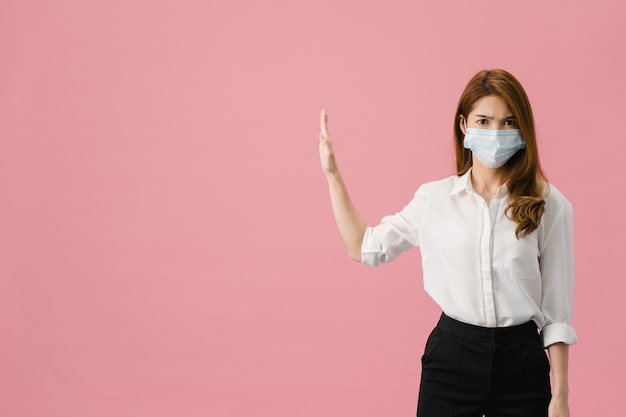 若いアジアの女性は、否定的な表現で手のひらで歌うのをやめ、青い背景に分離されたカメラを見て医療フェイスマスクを着用します。