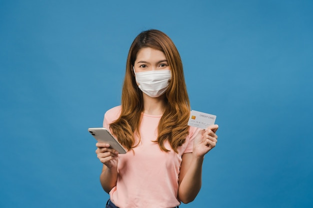 Young asia lady wearing medical face mask using phone and credit bank card with positive expression, smiles broadly, dressed in casual clothing and stand isolated on blue wall