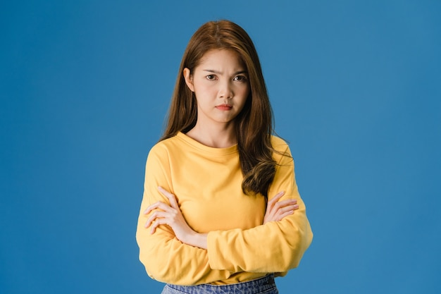 Young asia lady with negative expression, excited screaming, crying emotional angry in casual clothing and looking at camera isolated on blue background. happy adorable glad woman rejoices success.