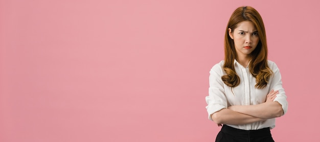 Young asia lady with negative expression, excited screaming, crying emotional angry in casual clothing and looking at camera isolated on pink background. Free Photo