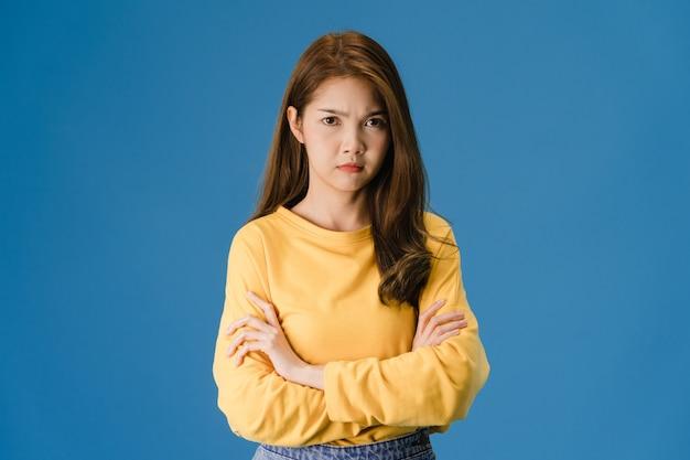 否定的な表現で若いアジア女性興奮して叫んで、カジュアルな服装で感情的な怒りを泣いて、青の背景に分離されたカメラを見てします。幸せな愛らしい喜んで女性は成功を喜ぶ。