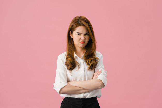 부정적인 표정으로 젊은 아시아 아가씨, 흥분된 비명, 캐주얼 의류에 감정적 인 화가 울고 분홍색 배경에 고립 된 카메라를보고.