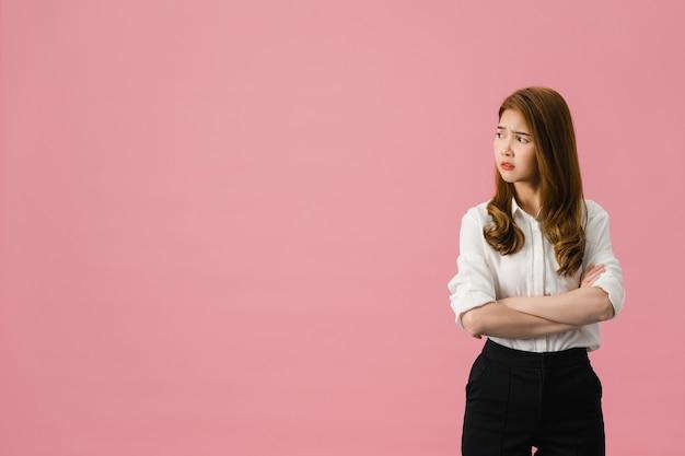 부정적인 표현, 흥분된 비명, 캐주얼 의류에 감정적 인 화가 울고 분홍색 배경에 고립 된 공간을보고 젊은 아시아 아가씨.