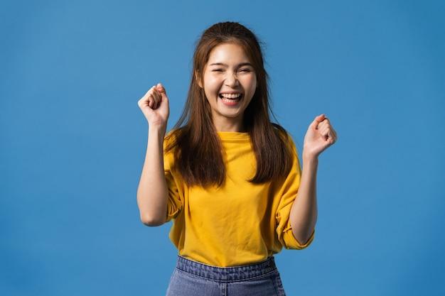 前向きな表情で、楽しくてエキサイティングな若いアジアの女性。カジュアルな布に身を包み、青い背景にカメラ目線します。幸せな愛らしい喜んで女性は成功を喜ぶ。顔の表情のコンセプト