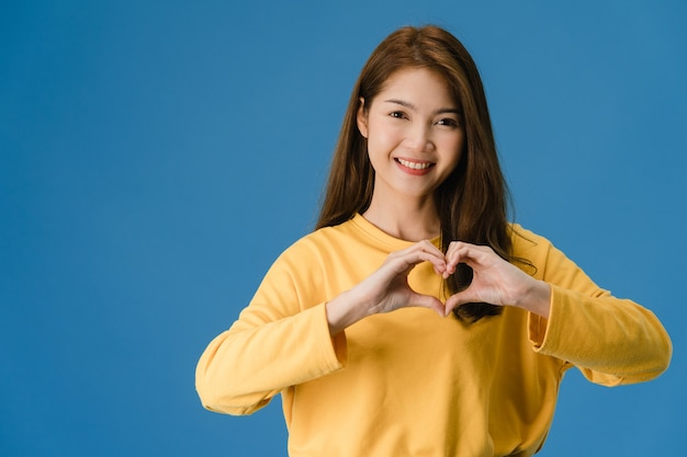 Young asia lady with positive expression, shows hands gesture in heart shape, dressed in casual clothing and looking at camera isolated on blue background. happy adorable glad woman rejoices success.