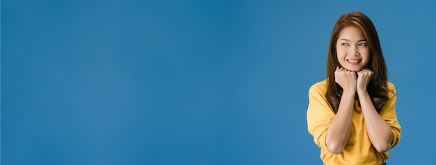 Giovane donna asiatica con espressione positiva, sorriso ampiamente, vestita in abbigliamento casual isolato su sfondo blu. la donna felice adorabile felice si rallegra del successo. sfondo banner panoramico con spazio di copia
