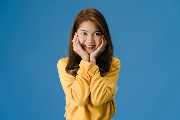 肯定的な表現を持つ若いアジア女性、広く笑顔、カジュアルな布に身を包んだし、青色の背景に分離されたカメラを見てください。幸せな愛らしい喜んで女性は成功を喜ぶ。顔の表情のコンセプトです。