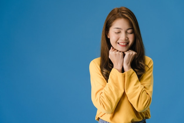 Молодая дама азии с позитивным выражением лица, широко улыбается, одетая в повседневную одежду и закрывает глаза на синем фоне. счастливая очаровательная рада женщина радуется успеху. концепция выражения лица.