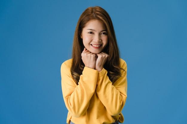 肯定的な表現を持つ若いアジア女性、広く笑顔、カジュアルな服を着て、青い背景にカメラを見てください。幸せな愛らしい喜んで女性は成功を喜ぶ。顔の表情のコンセプトです。