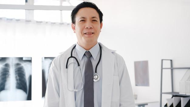 청진 기 카메라, 미소와 팔을보고 흰색 의료 제복을 입은 젊은 아시아 남성 의사가 건강 병원에서 환자와 화상 회의를하는 동안 건넜다.