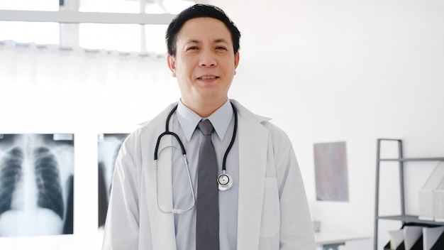 Young asia male doctor in white medical uniform with stethoscope looking at camera, smile and arms crossed while video conference call with patient in health hospital.