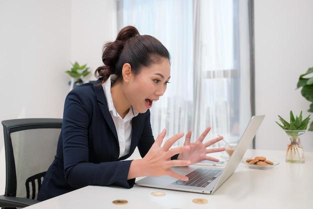 Молодая азиатская современная успешная деловая женщина с компьютером и биткойнами в столе, концепция биткойнов