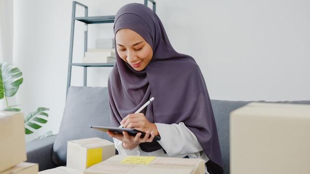Молодая азиатская мусульманская бизнес-леди проверяет заказ на поставку продукта на складе и сохраняет на планшетном компьютере работу в домашнем офисе.