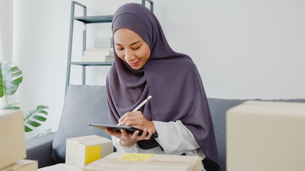 Young asia muslim businesswoman check product purchase order on stock and save to tablet computer work at home office.