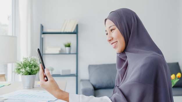 Young asia muslim businesswoman using smart phone talk to friend by videochat brainstorm online meeting while remotely work from home at living room.