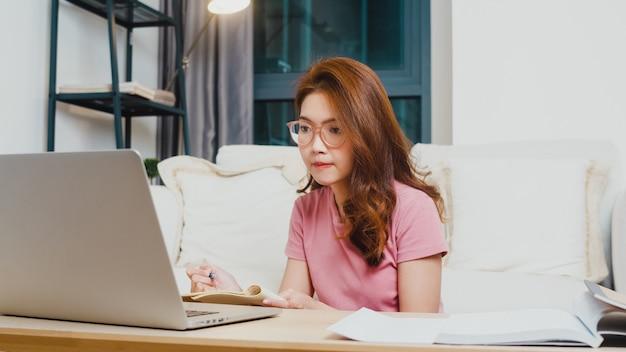 オンラインアジアの若いアジアの10代の少女学生遠隔学習レッスンと夜自宅からリビングルームでコンピューターのラップトップで勉強します。社会的距離、コロナウイルス防止のための検疫。