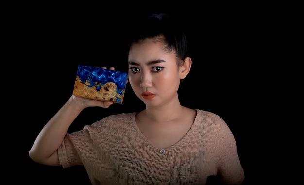Молодая азиатская женщина, держащая эпоксидную смолу с деревянной палкой из капа и клена на черном фоне