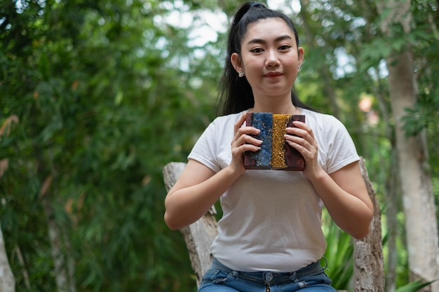 バールメープルウッドスティックとエポキシ樹脂を持っている若いアジアの女性の手