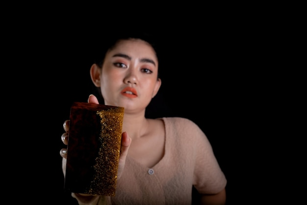 黒の背景にバールメープルウッドスティックと金エポキシ樹脂を持っている若いアジアの女性の手