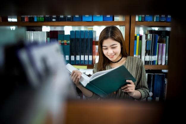 公共図書館で緑の本を持っている若いアジアの女性。