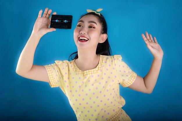 青い背景にカセットテープを保持しているレトロなファッションの黄色いドレスの若いアジアの女性