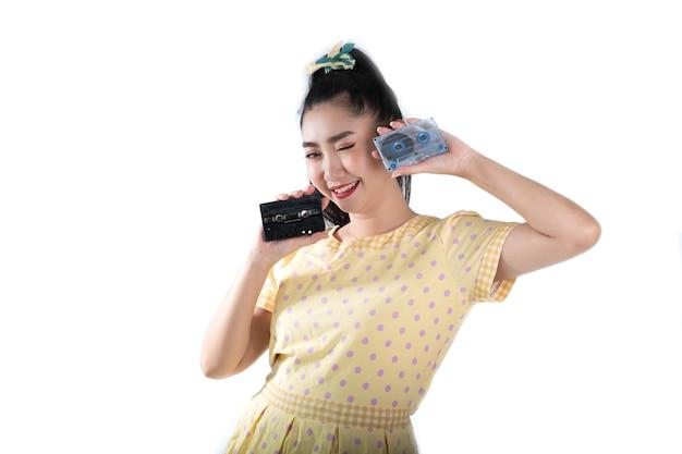 白い背景の上のカセットテープを保持しているレトロなファッションの黄色いドレスの若いアジアの女性