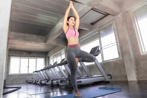 Young asia woman practicing yoga with sportswear bra and pants at fitness gym