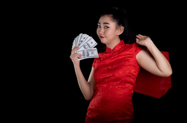 Молодая азиатская женщина в красном платье в традиционном cheongsam держит сумку для покупок и денежную купюру 100 долларов сша