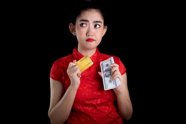 Молодая азиатская женщина в красном платье в традиционном чонсаме держит кредитную карту и денежную купюру 100 долларов сша