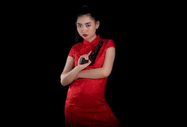 젊은 아시아 여자 빨간 드레스 전통 치파오 총을 들고