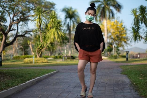 立って医療マスクを身に着けている若いアジアの女性