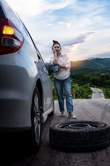 公道で助けを求めるために車の近くに立っている若いアジアの女性