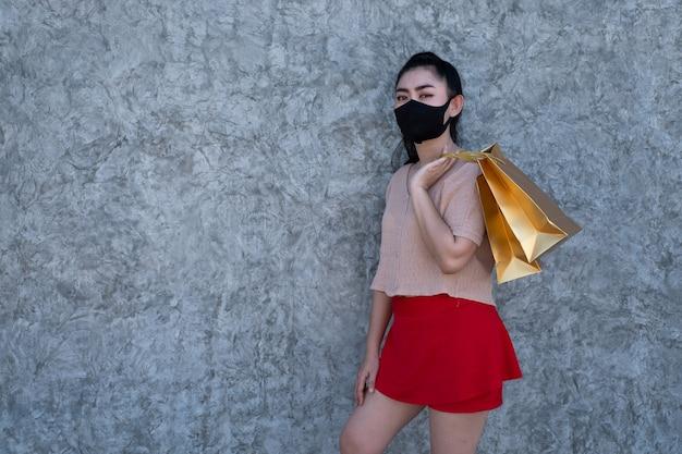 コンクリートの壁の背景に買い物袋を保持しているフェイスマスクを身に着けている若いアジアの女性