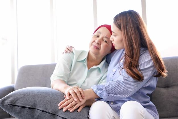 암과 싸우는 머리 스카프를 착용 한 그녀의 어머니와 함께 젊은 아시아 여성이 소파에 앉아 그녀의 팔이 어머니를 감싸고 있습니다.