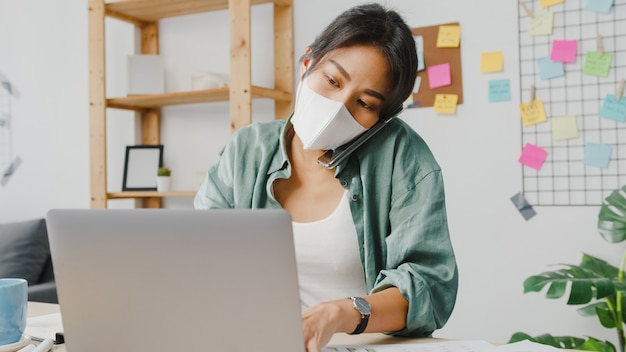 若いアジアの女性は、居間で遠く離れて働いている忙しい起業家に電話で話している医療用フェイスマスクを着用しています。