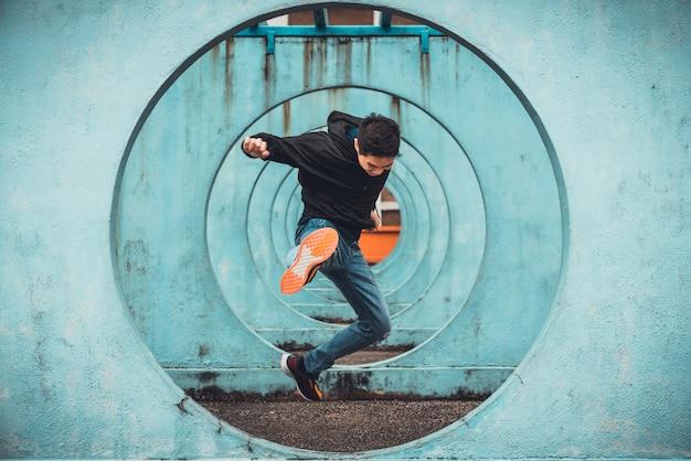 Молодой азиатский активный человек прыгает и пинает действие