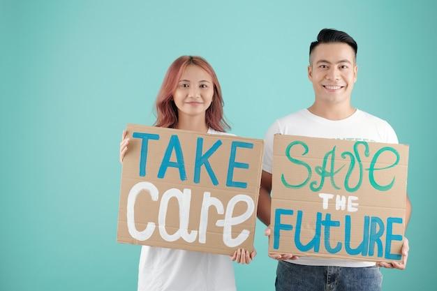 Молодые азиатские активисты держат две картонные таблички с осторожностью и спасают будущие надписи