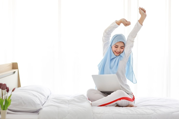 Young asian arab woman using laptop sitting on bed in bedroom.