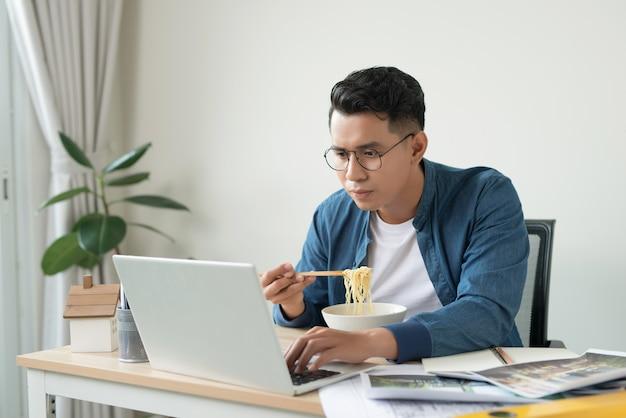 Молодой азиатский архитектор ест лапшу в офисе. на рабочем столе