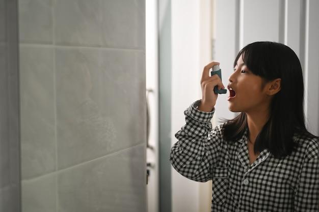 Молодая азиатская девушка, больная астмой, использует ингалятор для лечения одышки и хрипов.