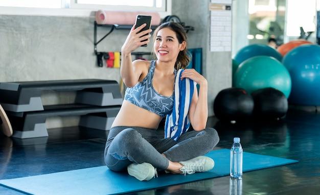 Молодой азиатский привлекательный улыбающийся активный фитнес, сидя на полу в тренажерном зале и принимая селфи.