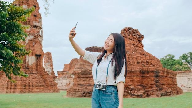 若いアジアのバックパッカーブロガーの女性が自分撮りをします