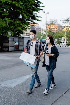 Молодая азиатская пара пеших туристов в маске, защищающей от коронавируса, держится и проверяет местоположение на бумажной карте во время прогулки по городской улице, красивая женщина держит смартфон в руке