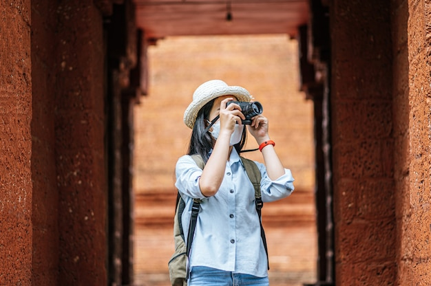 Young asian backpacker female wearing hat and protection mask while traveling in historic site