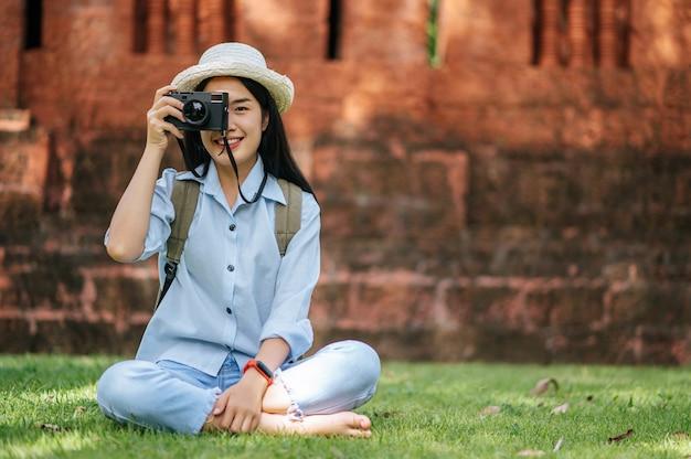 Giovane donna asiatica backpacker che indossa un cappello sorridente mentre ha un viaggio in un sito storico, si siede sull'erba per rilassarsi e usa la fotocamera per scattare una foto con felice