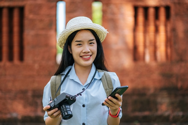 Young asian backpacker female wearing hat traveling in historic site, she use smartphone and camera take a photo with happy