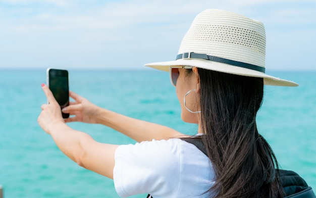 Young asian backpacker woman wear hat use smartphone taking selfie at pier. summer vacation at tropical paradise beach. happy hipster girl travel on holiday. summer vibes.