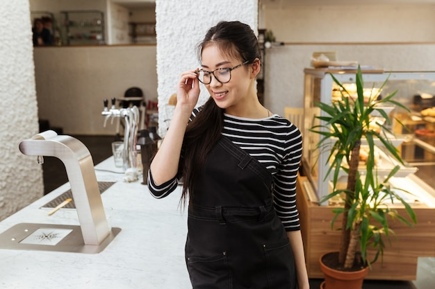 Young asian barmaid in eyeglasses