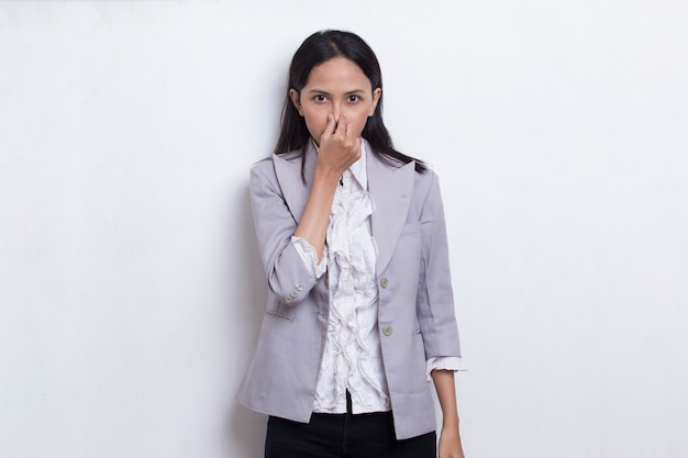 Young asian beautiful business woman holding her nose because of a bad smelling something
