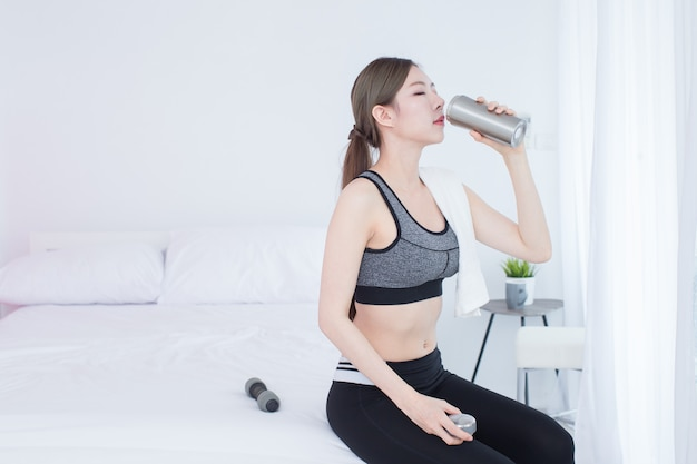 Young asian beautiful fitness girl drinking bottle of water after workout